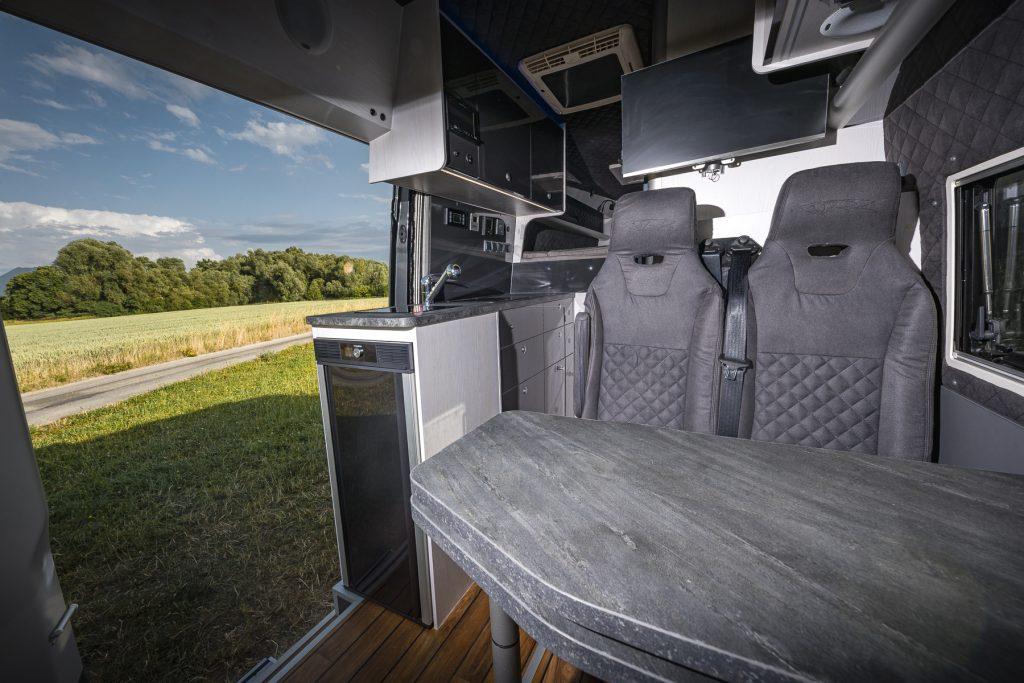 MAN TGE - Wohnbereich2 Küche Kühlschrank Sitzbank Steintisch Satellitenfernseher Klima Radio - VR-Motorhomes 2022